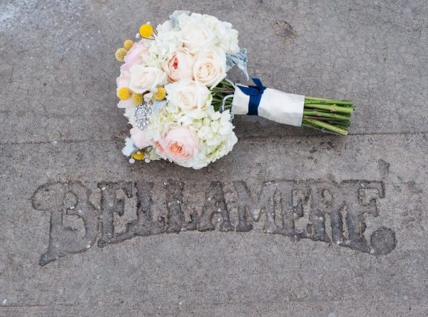 A wedding bouquet sits on the stone sidewalk above the engraved words Bellamere
