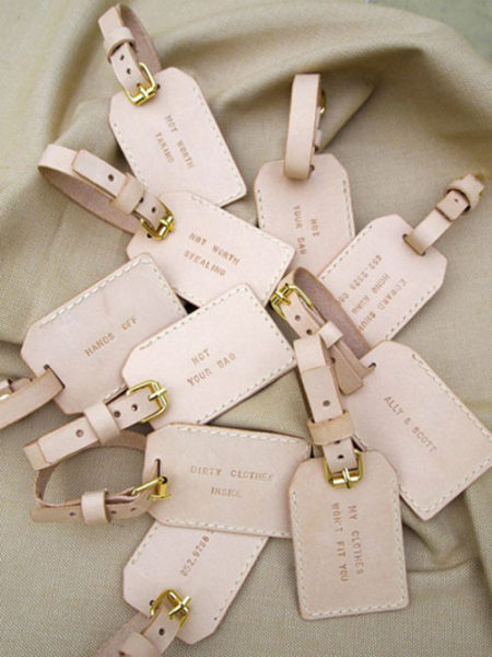 Leather travel bag tags with custom sayings sit on material.