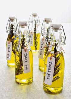 Oil in a glass bottle with a herb inside for flavour. A thank you label hangs off it.