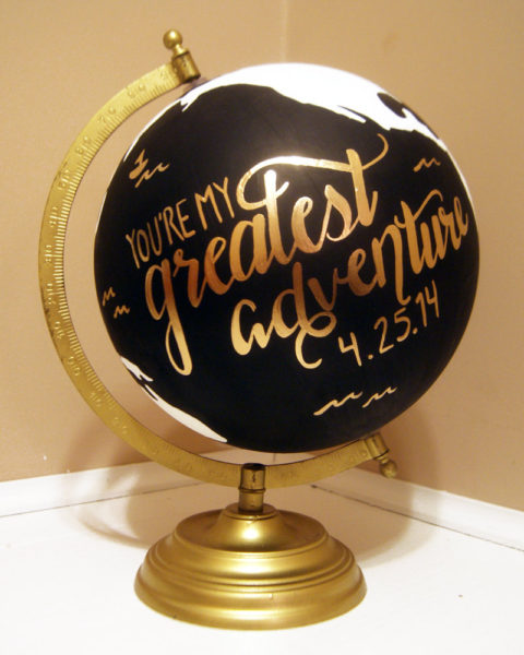 A black globe has a custom wedding message across the ocean. Plus guest signatures.