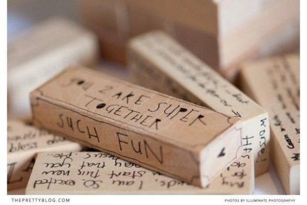 Jenga pieces are sprawled over the table with memories and quotes from the guests written on them.