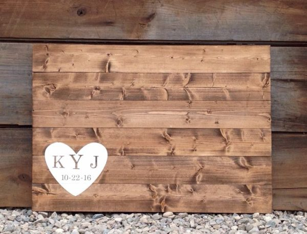 A light large wooden sign with a heart in the lower left side with the couples initials and wedding date