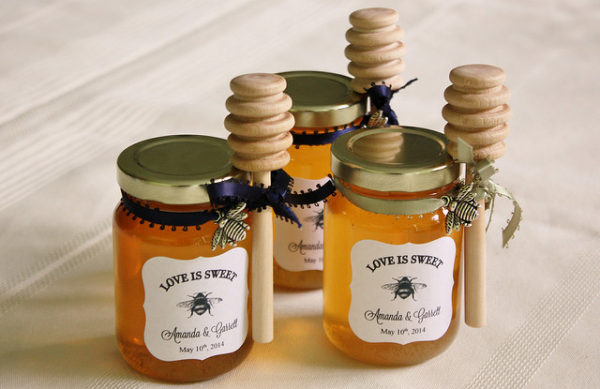 Honey in mason jars with custom wedding logos. Honey sticks are tied onto each.
