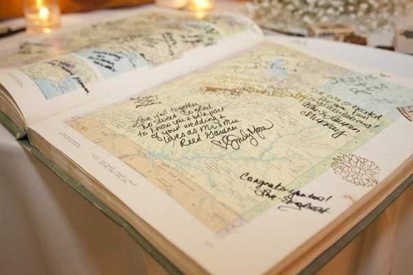 An old aged atlas is signed by the wedding guests across the pages.