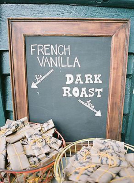A chalkboard sign behind custom wrapped coffee bean bags.