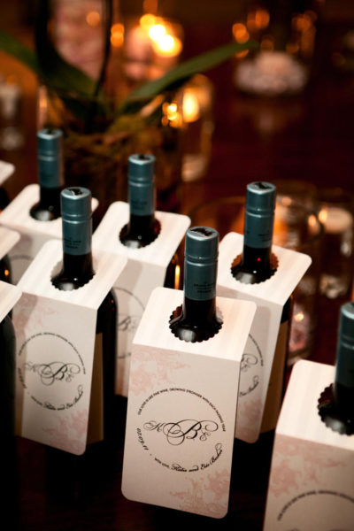 Wine bottles line a table with custom hanging labels.