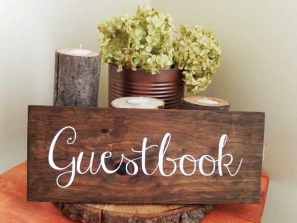 A dark wooden sign with the words guest book on it. With candles and plants behind