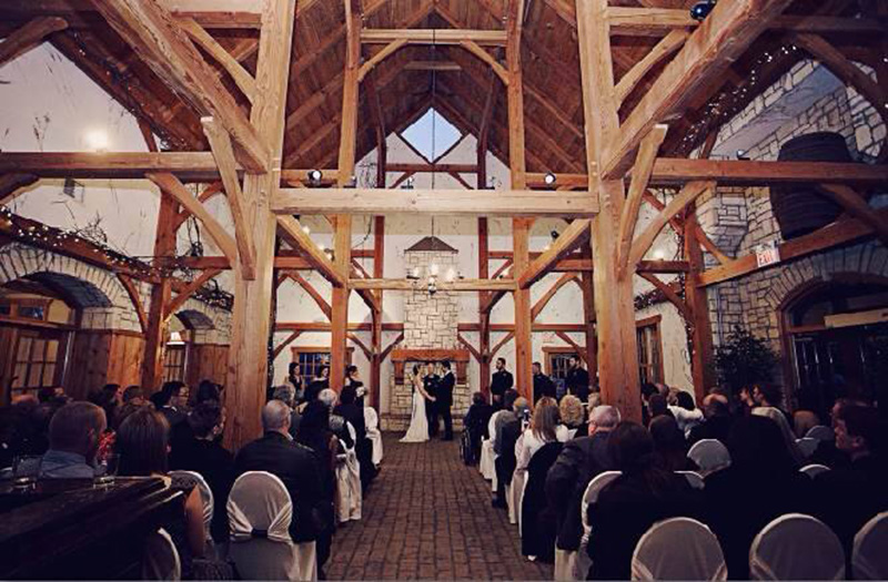 Bellamere Winery London Ontario Wedding Venue Indoor Ceremony Vintage Rustic Decor Exposed Beans Wine Barrels Ceremony Romantic Vows First Kiss Love