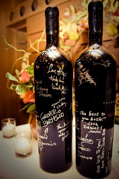 Magnum black wine bottles are signed in silver pen as a guest book.